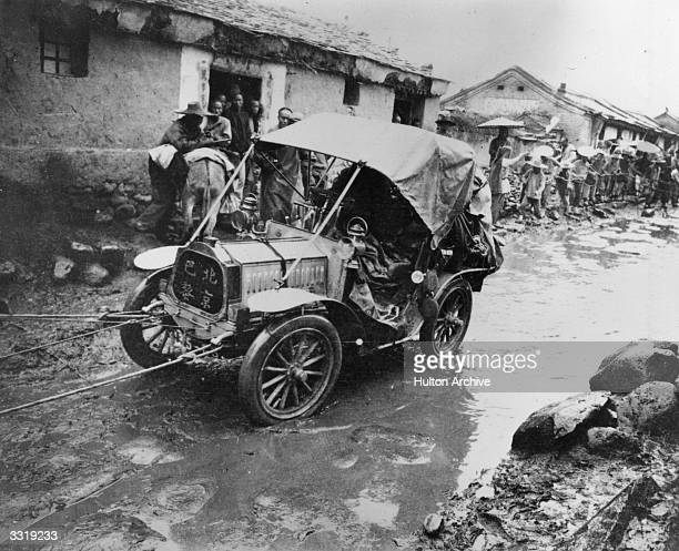 De Dion Bouton one of the competitors in the Peking to Paris road race is towed along a muddy street