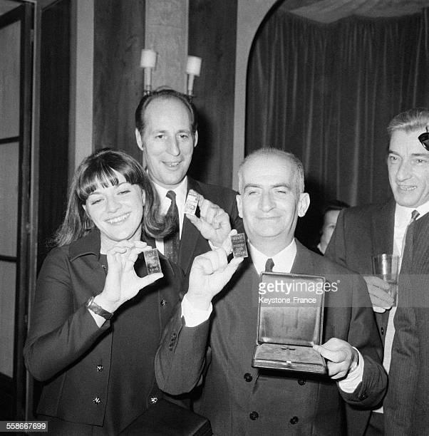 De gauche à droite AnneMarie Peysson Jean Girault et Louis de Funès photographiés avec leur ticket d'or à Paris France le 8 décembre 1967