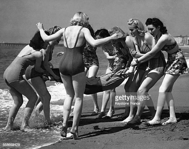 De jeunes femmes en maillot de bain porte un homme tout habillé pour le mettre à l'eau