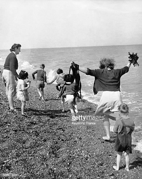 De jeunes Londoniens courent au bord de l'eau pour leur découverte de la mer dans le Kent à Kingsdown RoyaumeUni
