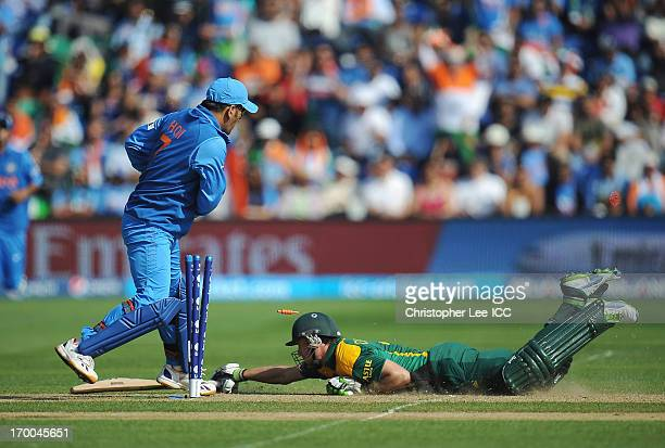 AB de Villiers of South Africa dives to stay in as Mahendra Singh Dhoni of India tries to run him out during the ICC Champions Trophy group B match...