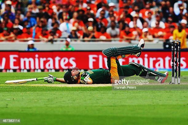 AB de Villiers of South Africa falls over after diving into his crease during the 2015 Cricket World Cup Semi Final match between New Zealand and...