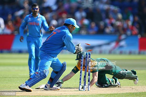 AB de Villiers of South Africa narrowly makes his ground as MS Dhoni of India breaks the wickets during the Group B ICC Champions Trophy match...