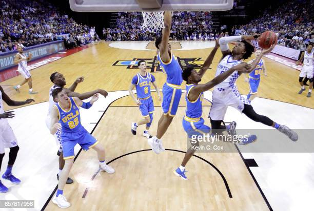 De'Aaron Fox of the Kentucky Wildcats drives to the basket against Isaac Hamilton and Ike Anigbogu of the UCLA Bruins in the first half during the...