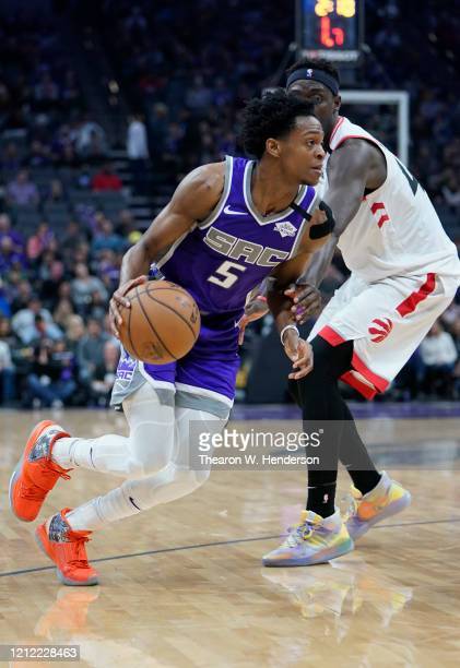 De'Aaron Fox of the Sacramento Kings dribbles the ball pass Pascal Siakam of the Toronto Raptors during the first half of an NBA basketball game at...