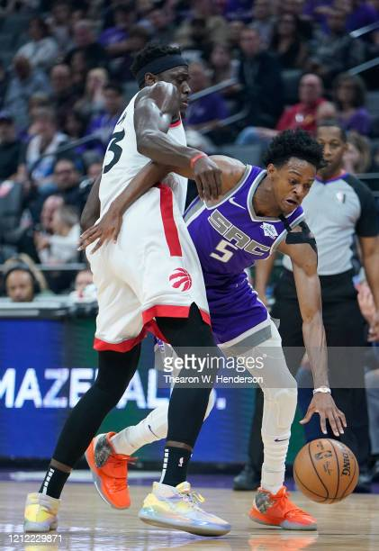 De'Aaron Fox of the Sacramento Kings dribbles the ball while being closely guarded by Pascal Siakam of the Toronto Raptors during the first half of...
