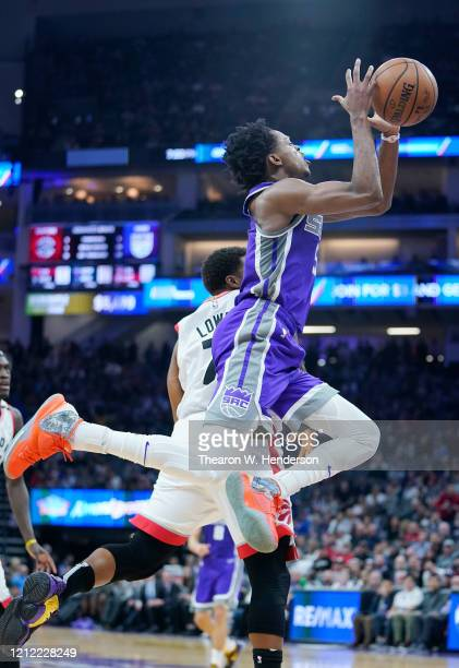 De'Aaron Fox of the Sacramento Kings drives on Kyle Lowry of the Toronto Raptors and gets fouled going up to shoot during the first half of an NBA...