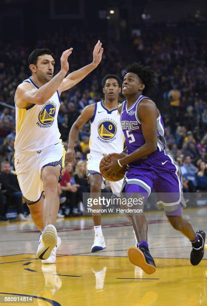 De'Aaron Fox of the Sacramento Kings drives towards the basket on Zaza Pachulia of the Golden State Warriors during their NBA basketball game at...