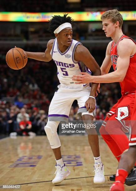 De'Aaron Fox of the Sacramento Kings looks to pass against Lauri Markkanen of the Chicago Bulls at the United Center on December 1 2017 in Chicago...