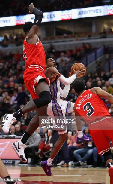 De'Aaron Fox of the Sacramento Kings puts up a shot between Bobby Portis and Shaquille Harrison of the Chicago Bulls on his way to a game-high 25...