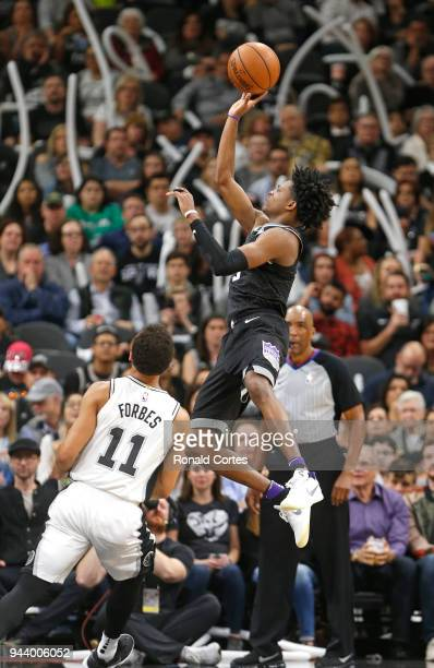 De'Aaron Fox of the Sacramento Kings shoots next to Bryn Forbes of the San Antonio Spurs at ATT Center on April 9 2018 in San Antonio Texas NOTE TO...