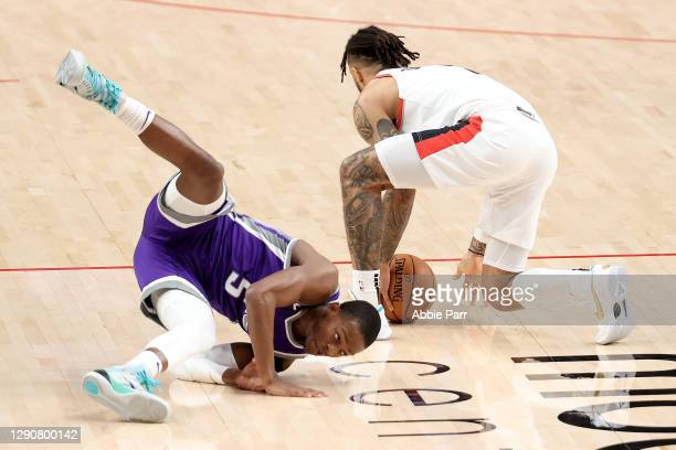 De'Aaron Fox of the Sacramento Kings turns the ball over to Gary Trent Jr. #2 of the Portland Trail Blazers in the second quarter during their...