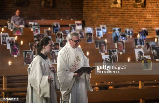 Deacon Bernd Malecki and server Anna hold an Easter service in front of portraits of believers who could not attend the mass due to the novel...