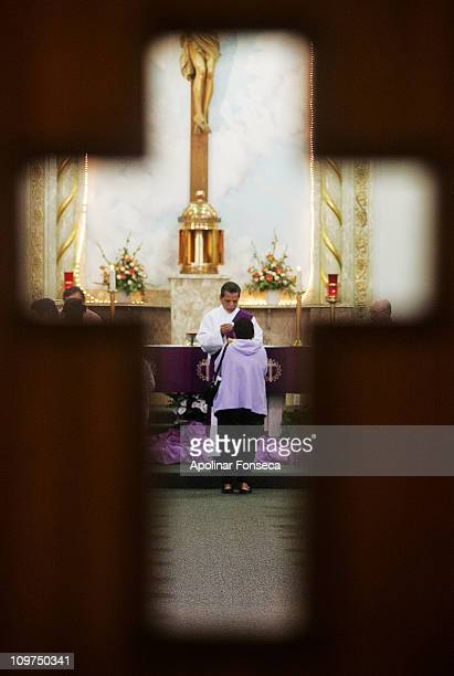 Deacon Leonard Rodriguez gives communion during the noon Ash Wednesday Mass at Immaculate Heart of Mary Church. He is seen through a cutout on a...