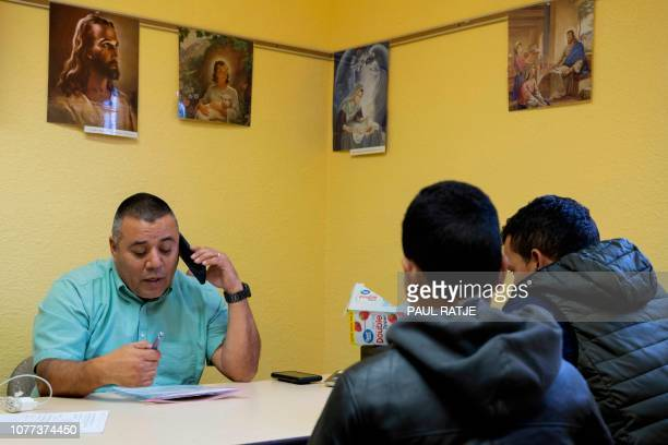 Deacon Leonel Briseno who coordinates Project Oak Tree at numerous parishes around Las Cruces New Mexico assists a migrant father and son book plane...