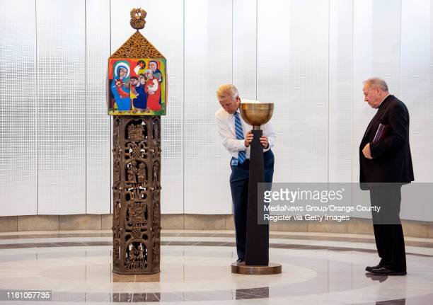 Deacon Mike Stock, center, places the Sanctuary Lamp near the Tabernacle under the direction Fr. Christopher Smith, right, at Christ Cathedral in...