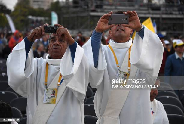 Deacons take pictures as they wait for the arrival of Pope Francis at O'Higgins Park in Santiago on January 16 2018 where the pontiff will officiate...
