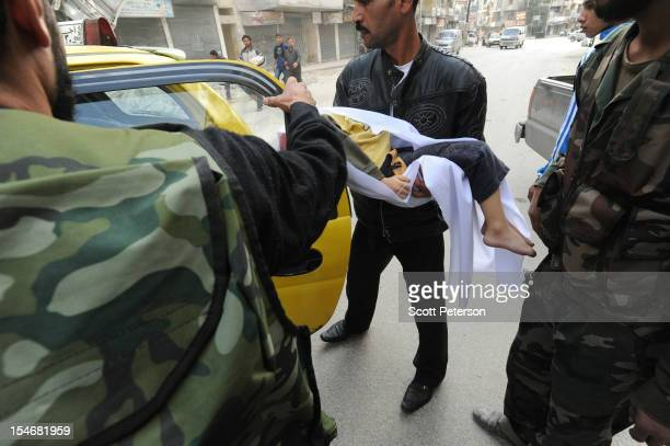 A dead 7yearold Syrian girl is loaded into a taxi as the intense human and material cost grows from three months of intense fighting against rebels...