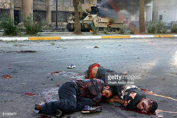 Dead and critically injured Iraqi civilians are seen lying in the street as a US military vehicle burns in the background on September 12 2004 in...