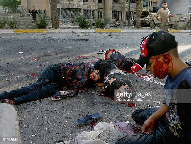 Dead and injured Iraqi civilians are seen lying in the street on September 12 2004 in Haifa Street Baghdad Iraq Fighting broke out in the early hours...
