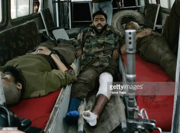 A dead and wounded Indian policemen lies inside an ambulance outside a hospital on January 15 2010 in Srinagar India Two people were killed including...