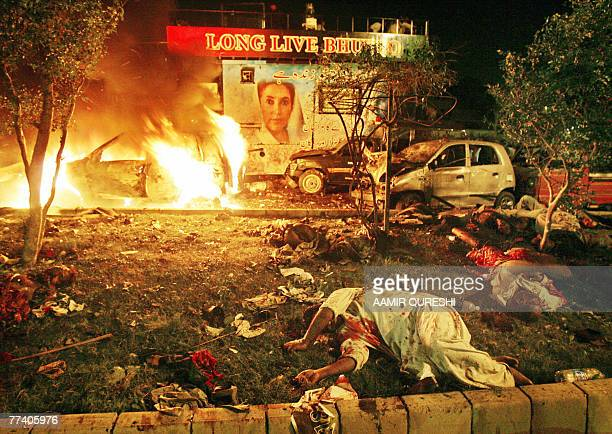 Dead bodies lie in front of burning vehicles and a poster of former Pakistani prime minister Benazir Bhutto after suicide attacks in Karachi 18...