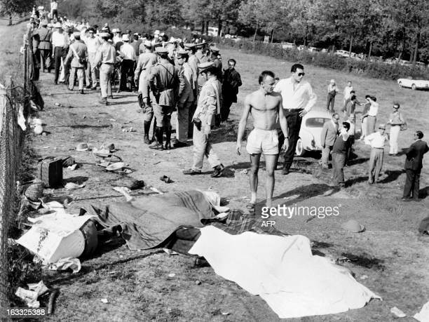Dead bodies lie on the ground as policemen try to evacuate people from the scene of the accident caused by German driver Wolfgang von Trips whose...