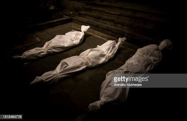 Dead bodies wrapped in protective cover of patients who died of the Covid-19 coronavirus disease are kept on the ground waiting to be cremated at a...