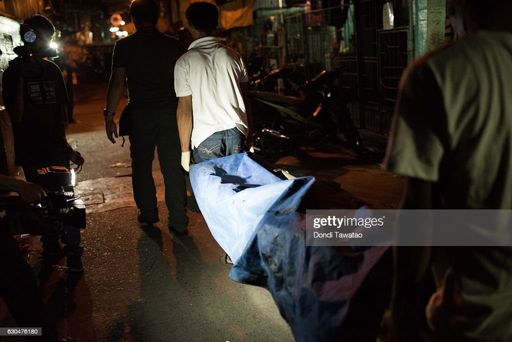 A dead body is brought out by morgue workers during an alleged buy bust operation by police which killed two suspects on December 23, 2016 in Manila, Philippines. Philippine president Rodrigo Duterte has said he wanted the Constitution amended to allow Philippine leaders to wield martial law powers without judicial and congressional approval, a move he said is necessary to contain the ongoing 'drug menace' and maintain peace and security in the country. Around 5,882 people have been killed across the country since President Rodrigo Duterte launched his war on illegal drugs five months ago, according to figures from the Philippine National Police. An average of 25 victims were killed daily during the five-month period, and police kill 97 percent of those they shoot, leaving 33 dead for every person wounded according to the figures. Last October, Duterte himself said the country could expect about 20,000 or 30,000 more deaths in his administration's bloody war on drugs.