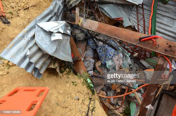 A dead body is seen amongst the rubble at the landslide site in Naga City on the popular tourist island of Cebu on September 20 2018 At least three...