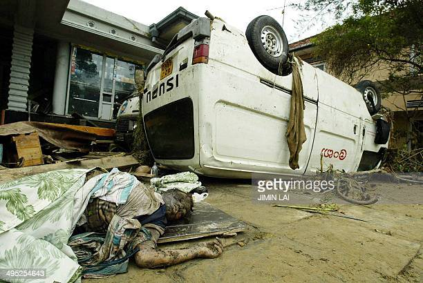 A dead body lies next to an overturned van in the Galle district in the southwestern coast of Sri Lanka 27 December 2004 Sri Lanka launched a massive...