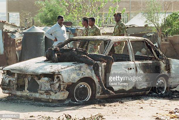Dead Body of a Policeman on a Charred Vehicle