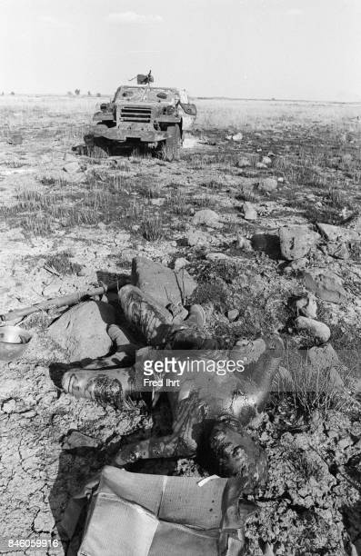 Dead burned soldier laying on the ground close to his armored vehicle
