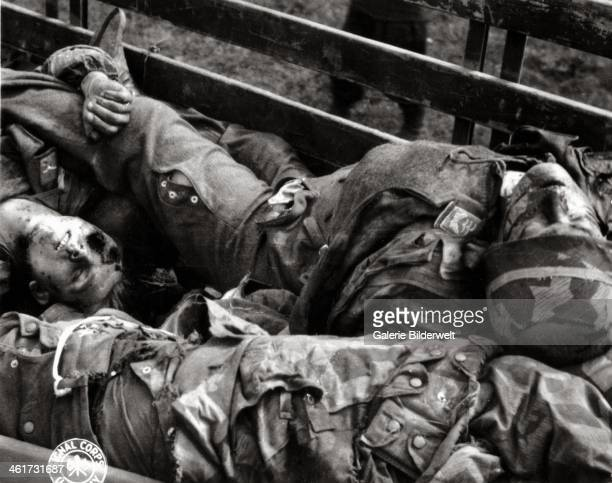 Dead German paratroopers are piled up in a cart. June 1944. Normandy, France.