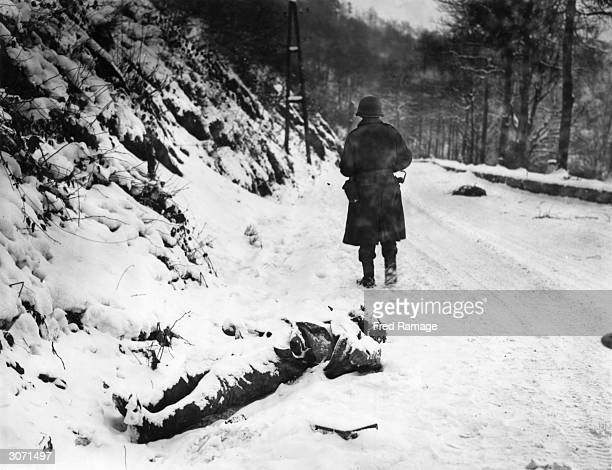 A dead German soldier covered in snow on the road to the town of La Roche in the northern half of the Ardennes which was captured by British and...