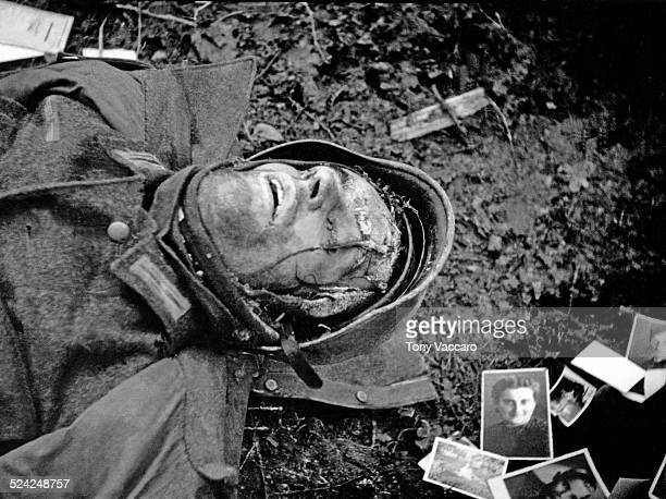 A dead German soldier killed during the Battle of the Bulge is seen surrounded by family photographs Hürtgen Forest Germany World War II December 1944