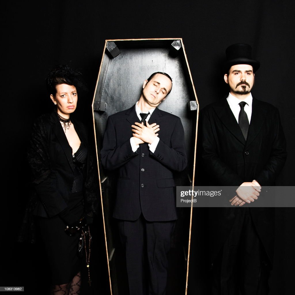 Dead husband in coffin with grieving wife and undertaker : Stock Photo