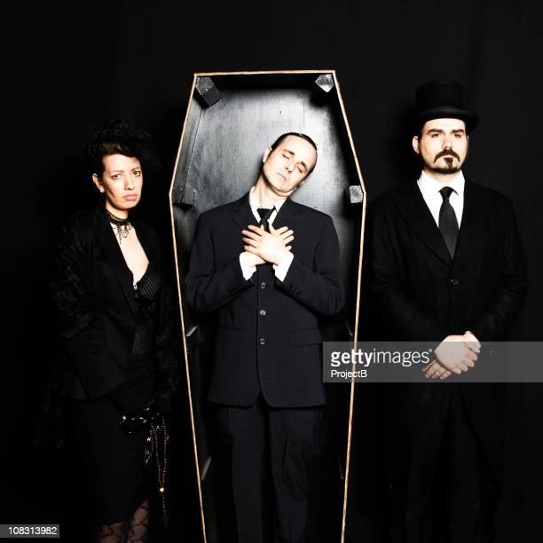 Morto marido em caixão com grieving esposa e Agente Funerário