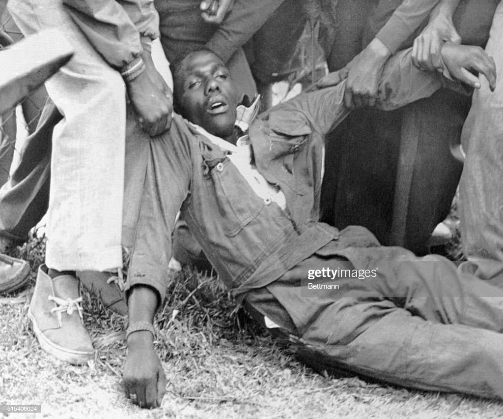 Dead in Rioting. Johannesburg, South Africa: Residents drag away a dead man in coveralls in the black township of Soweto after police fired into crowd of demonstrators, August 25. The deaths mount as anti-government violence continues.