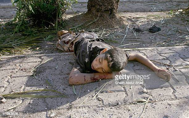 A dead Iraqi boy is seen lying in the street on September 12 2004 in Haifa Street Baghdad Iraq Fighting broke out in the early hours of September 12...