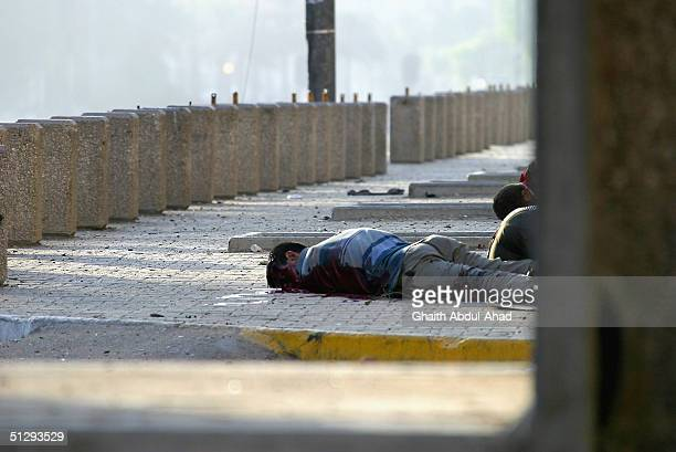 A dead Iraqi civilian is seen lying in the street on September 12 2004 in Haifa Street Baghdad Iraq Fighting broke out in the early hours of...