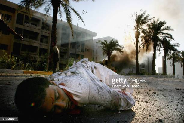 A dead Iraqi civilian lies in the street as a US military vehicle burns in the background on September 12 2004 in Haifa Street Baghdad Five Iraqi...