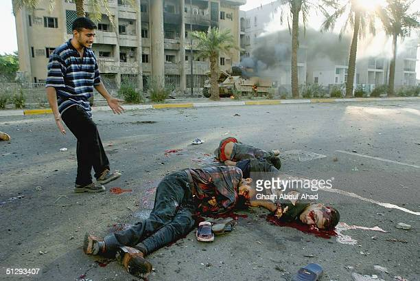 Dead Iraqi civilians are seen lying in the street as a US military vehicle burns in the background on September 12 2004 in Haifa Street Baghdad Five...