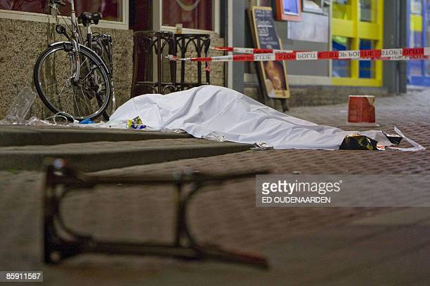 A dead man covered by a white blanket lays on the floor after a man pulled a gun and opened fire in a crowded cafe in the Dutch city of Rotterdam on...