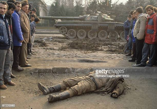 A dead member of Ceausescu's security team lies in front of a tank in Bucharest during the Romanian Revolution December 1989