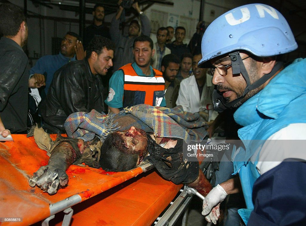 A dead Palestinian is carried to hospital at the Rafah refugee camp southern Gaza Strip May 20, 2004. Israel defied international fury at the killing of nearly 40 Palestinians in the Rafah refugee camp, a militant stronghold, to expand its bloodiest Gaza Strip raid in years on Thursday.