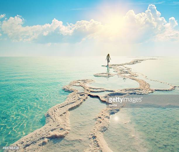 Silhouette of young woman walking on Dead Sea salt shore at sunrise towards the sun