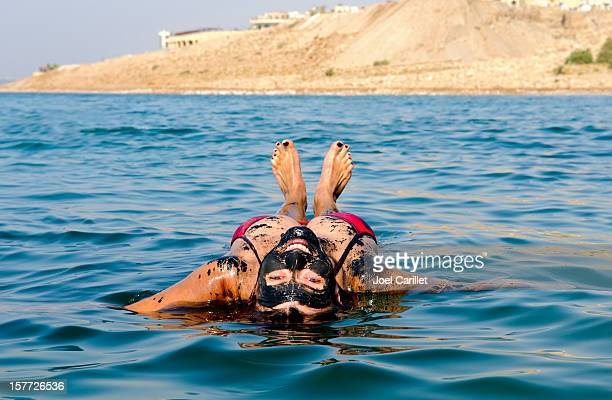 dead sea vacation with woman floating on back - dead sea stock pictures, royalty-free photos & images