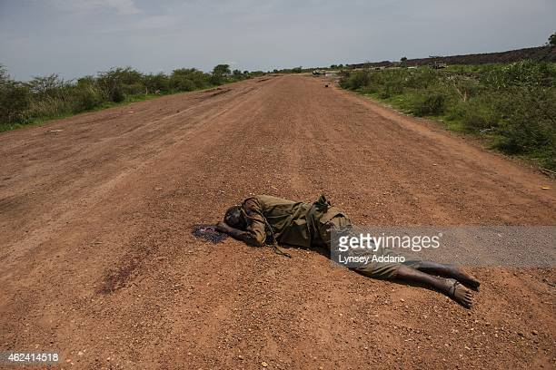 A dead SPLA government soldier lies in the road in front of the base of the United Nations Mission in South Sudan as government soldiers battle with...