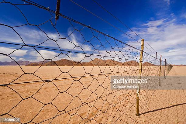 Dead straight farmer's wire fence, chain-link fencing over flat desert sand on the edge of the Namib Desert, Namibia, Africa